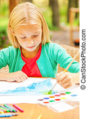 Performing her creativity. Cute little girl drawing something on paper while sitting at the table and outdoors