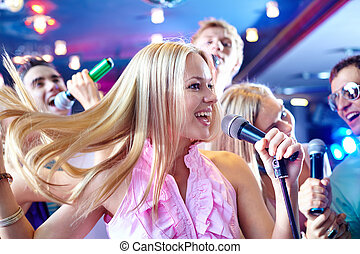 Performing song - Portrait of joyous girl singing at party...