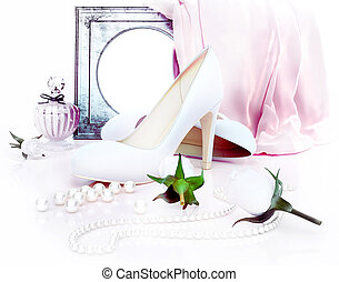 Perfume bottle, high heels, mirorr, roses and pearls located on light background. Wedding.