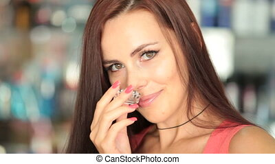 Perfume Shopping - Attractive woman smelling perfumes in...
