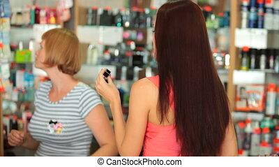 Perfume Shopping - Young woman choosing perfume in cosmetics...