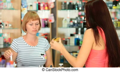 Perfume Shopping - Young woman choosing perfume in cosmetics...