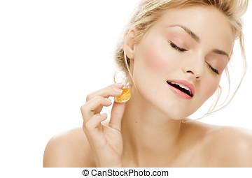 Perfume - Young woman applying perfume.