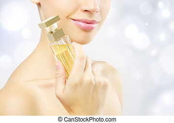 Perfume - Young woman with perfume on a light background