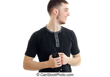 perky young guy with headphones and telephone turned his head to the side and laughs