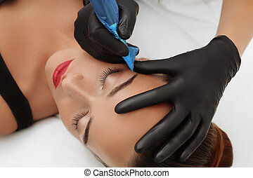 Permanent make up on eyebrows - Cosmetologist applying...