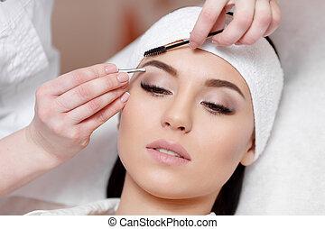 Beautiful young woman gets eyebrow correction procedure