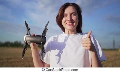 Permission to fly a drone. The operator of the quadcopter shows the like and the drone. Smiling girl with a drone in her hand.