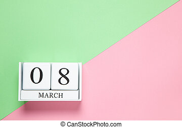 Perpetual calendar with date of March 8 on two-color background pink and green. Flat lay. Top view. International Happy Women's Day celebration concept. Horizontal, close-up, copy spase. For delivery