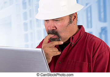 Hardhat worker perplexed, working on the tough issues with his laptop, he has a serious thoughtful look that he values his job, he is wearing red shirt and isolated on bluish background, copy space on hardhat and laptop