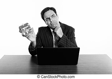Persian businessman thinking and holding house figurine while sitting with laptop on wooden table against white background
