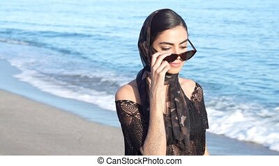 Persian woman enjoying the view of the sea on the beach. - ...