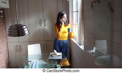 Persian woman using her smart phone near the window - ...