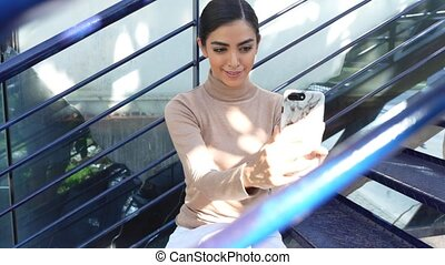 Persian woman using smartphone sitting on urban steps - ...