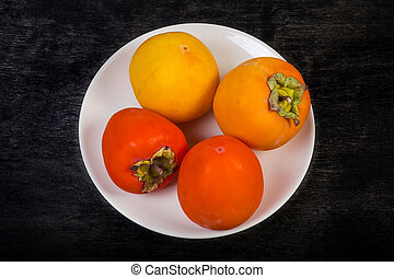Persimmon fruits on white dish on black background, top view
