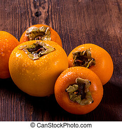 Persimmon on a wooden background with water drops, side view close-up, copy space