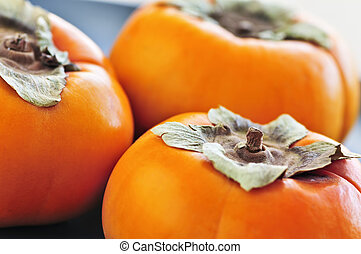 Orange whole ripe persimmon fruit on a plate