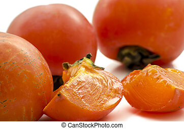 Ripe persimmons and two slices isolated on a white background.