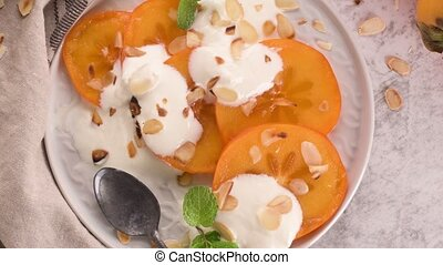 Persimon with yogurt and almonds - Sliced persimon with...