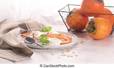 Persimon with yogurt and almonds - Sliced persimon with...