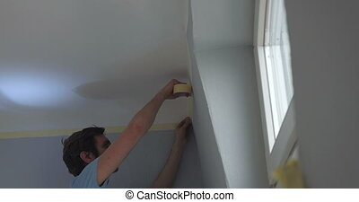 person attaching ribbon tape on wall