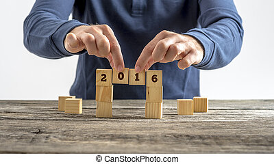 Person building a bridge of wooden cubes with the year 2016 sign