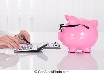 Person Calculating Bill With Pink Piggybank On Desk