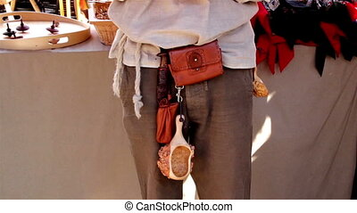 Person carrying scoop and hanging it on his waist band
