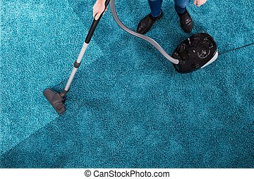 Person Cleaning Carpet With Vacuum Cleaner