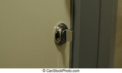 person closes the door on the latch