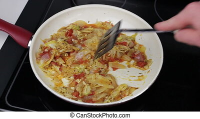 Person Cooking and Stirring Vegetables in a Pan - Tomatoes,...