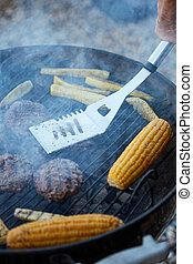 Person cooking fresh corn and patties on a BBQ