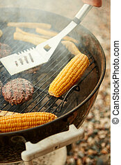 Person cooking meat and corncobs on a barbecue
