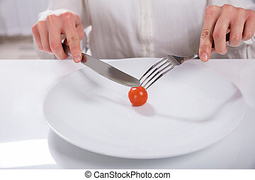Person Cutting Cherry Tomato On Plate