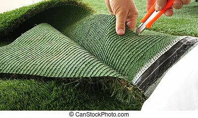 Person cutting sheet of artificial turf with knife