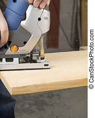 person cutting wooden plank with jigsaw cutter