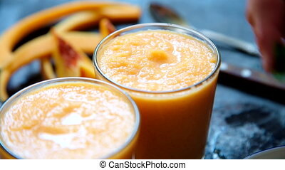 Person decorates orange smoothie - Close-up shot of person...