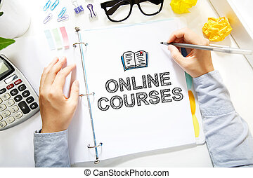 Person drawing Online Courses concepts on white paper in the...