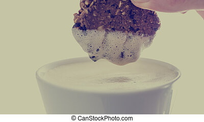 Person dunking a biscuit in a cup of coffee