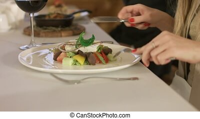 Person eating delicious salad in a restaurant