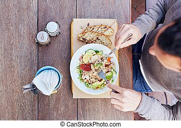 Person enjoying a fresh salad on their lunch break