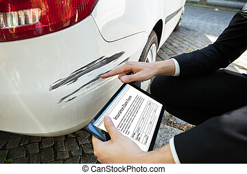 Person Examining Damaged Car While Filling Insurance Claim Form