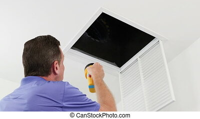 Person Examining HVAC Duct with a Flashlight - Male removes...