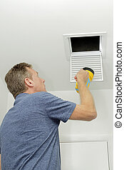 Person Examining Small Duct with a Flashlight
