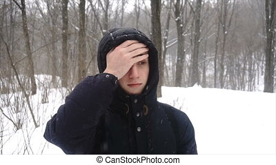 Person facepalming in slow motion 4K. Portrait shot of attractive male person making a facepalming pose with hand. Showing an expression of dismay, exasperation, embarrassment. shooting in the winter on the street, it snows