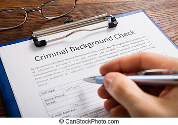 Person Filling Criminal Background Check Application Form
