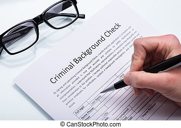 Person Filling Criminal Background Check Form
