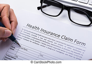 Person Filling Health Insurance Claim Form