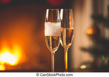Person filling two glasses with champagne. Burning fireplace and decorated Christmas tree