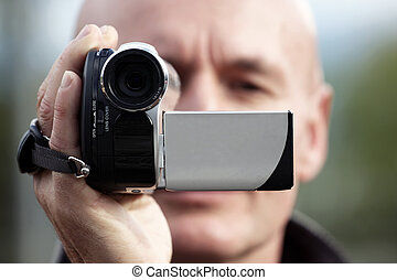 person filming a scene with a hand held camcorder